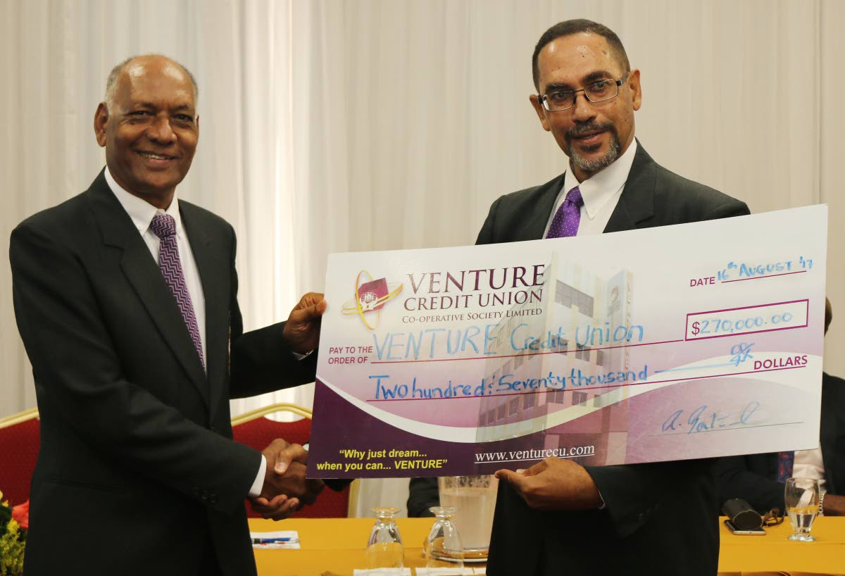 Lionel Sookoo (left), chairman of the 5k committee, collects a cheque valued at $270,000 from Roger Bertrand, president of Venture Credit Union, at yesterday's media conference.