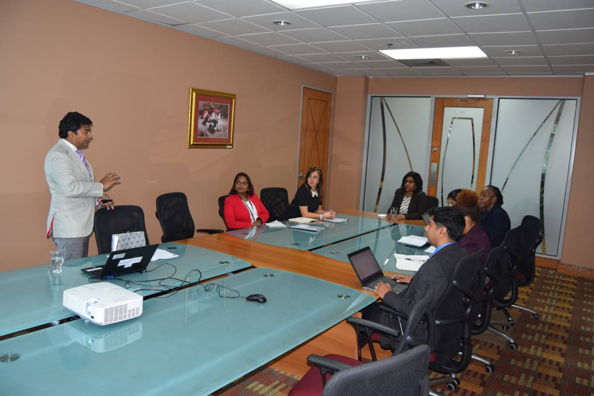 (Standing left) Director of the Trinidad and Tobago Fine Cocoa Company,  Ashley Parasram, shares an overview of the company's operations and opportunities for partnership, during a meeting with (fourth from left) Trade and Industry Minister, Paula Gopee-Scoon and members of the ministry's technical staff, during an August 15 meeting at the ministry's offices, Nicholas Tower, Port-of-Spain. This was the latest in a series of meetings being held by the ministry to examine new and innovative opportunities to boost exports and increase access to markets in agro processing. PHOTO COURTESY THE TRADE AND INDUSTRY MINISTRY.