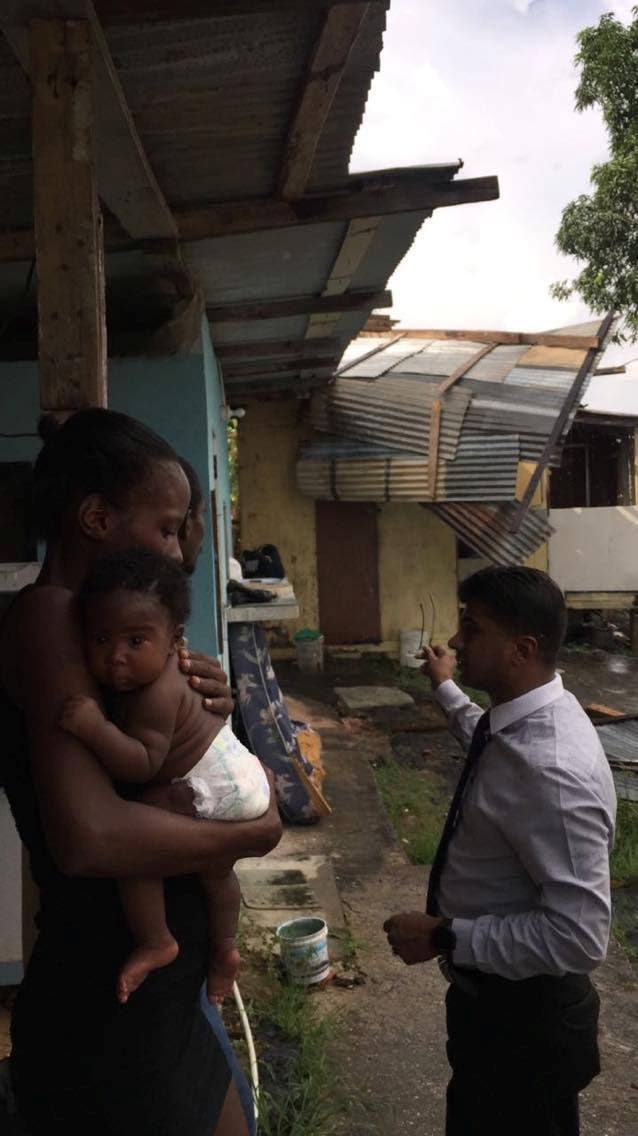 Alana Mayers and her 3-month-old baby girl Annesha Francis talking with Siparia Regional Corporation Chairman Dr GLEN Ramadharsingh at her home in Aripero Village, Rousillac, in the aftermath of a freak storm which tore off her roof yesterday.
