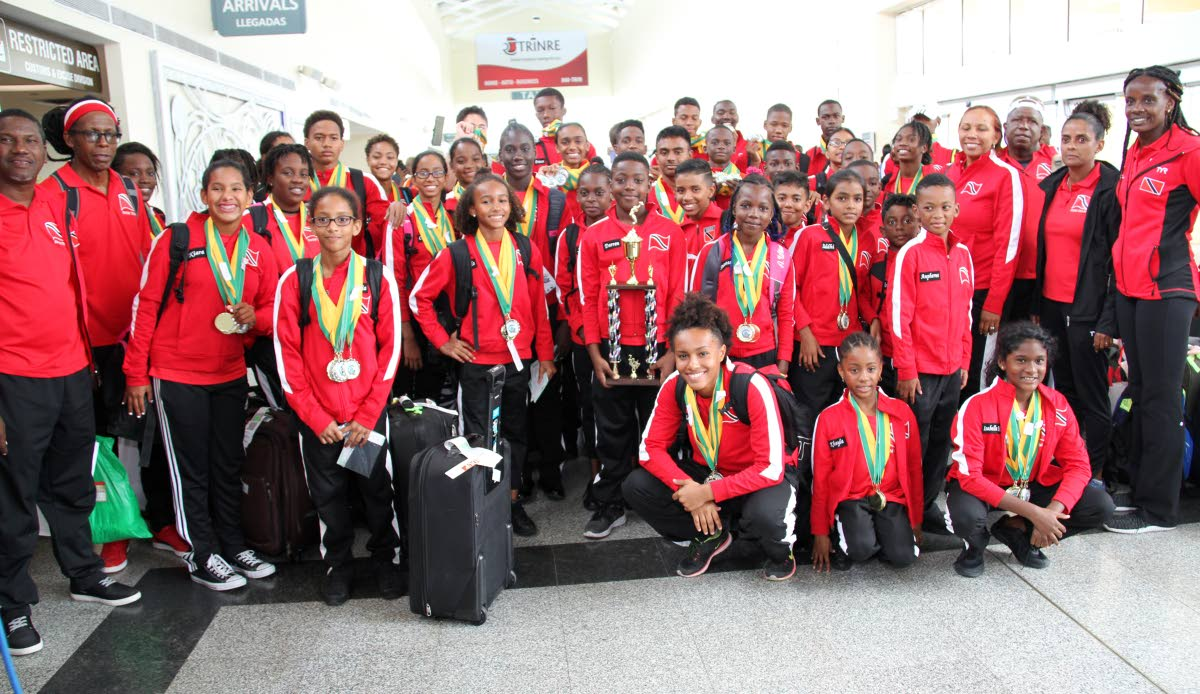 Members of Trinidad and Tobago's Goodwill swim team pose with their medals and overall trophy at the Piarco International Airport yesterday.