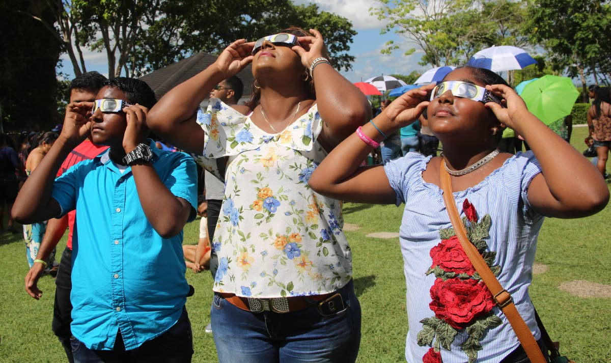 SUN-GAZING: The Jaichand family looks through their shades, which were provided by the TT Astro Club to look at the eclipse at from San Fernando Hill yesterday. At left is Vikash, his mother Sally Ann,centre, and sister Renushka Jaichand.