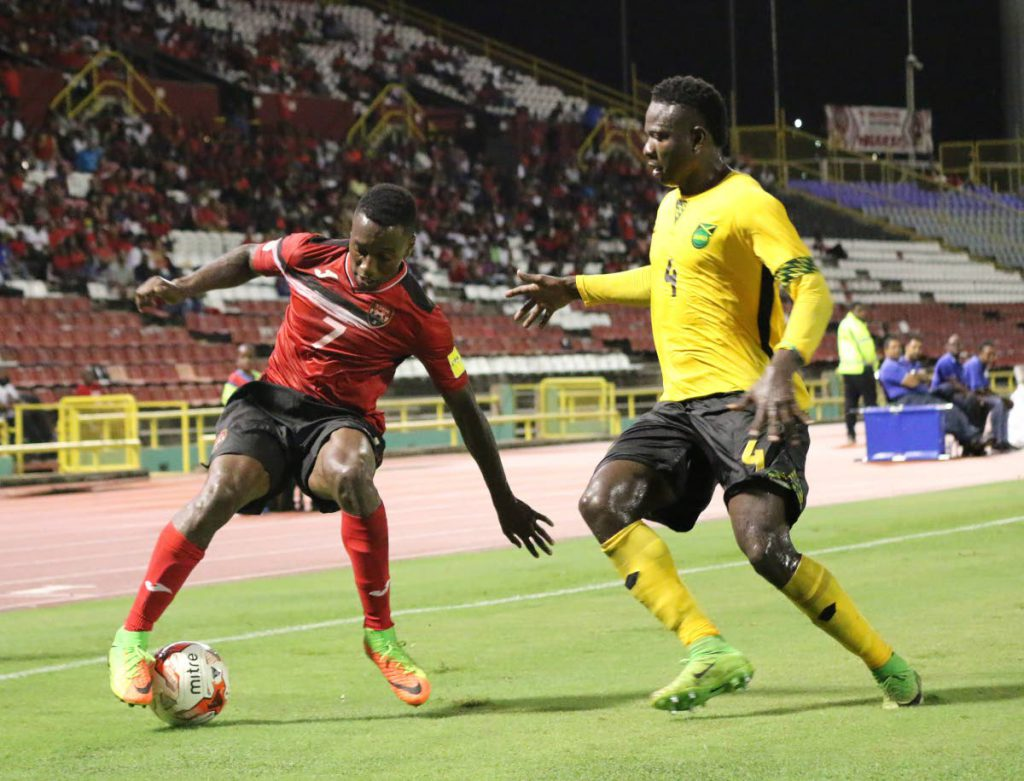 Cordell Cato of Trinidad and Tobago tries to get the better of Jamaica defender Ladale Richie during the first half of Thursday's friendly encounter at the Hasely Crawford Stadium, Mucurapo.