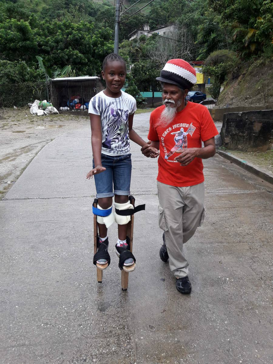 Junior Bisnath helps a girl learn how to walk on stilts.