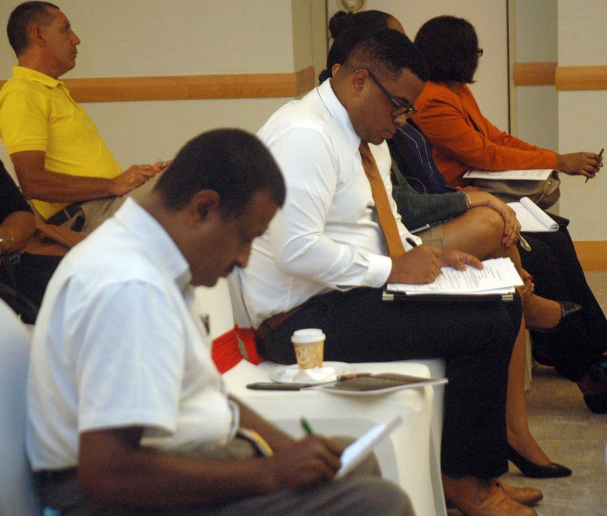 Shareholders of Scotia Investments Jamaica Limited, write their votes to decide if their stocks should be bought for 38 Jamaican dollars, at the HYATT Regency Hotel in Port-of-Spain, at a meeting for shareholders. Photo by Michael Joseph(NYLO Intern) 30-8-17