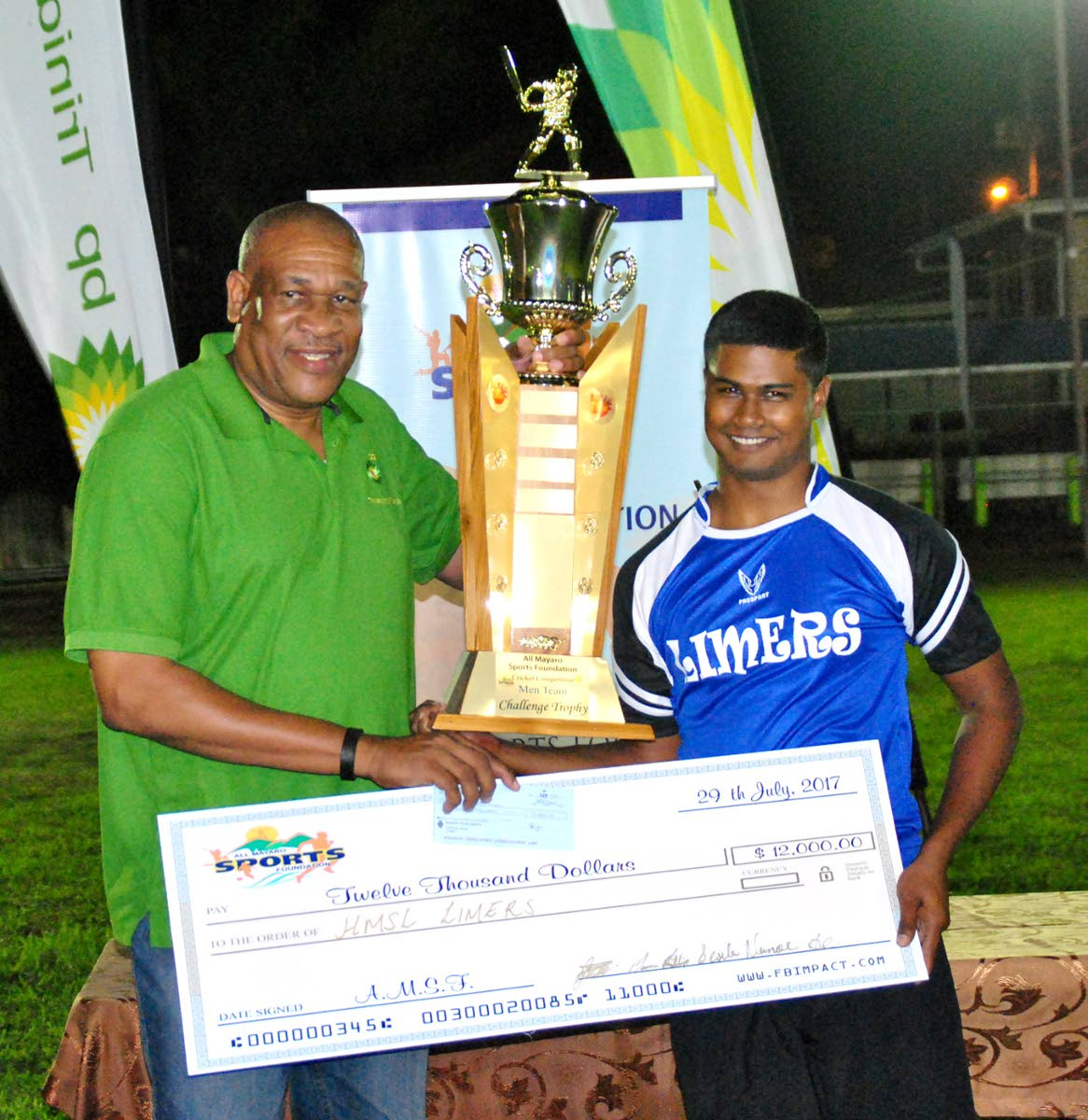 BPTT's Matthew Pierre (left) presents the coveted league championship trophy and winners' cheque to Mark Rampersad, captain of Limers, at the presentation of prizes in the 2017 BPTT Mayaro Night Windball Cricket League.
