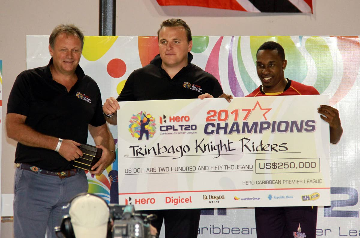 Dwayne Bravo, captain of the Trinbago Knight Riders, collect the US $250,000 cheque from CPL chief executive Damien O'Donohue (centre) while an unnamed CPL official looks on, during the presentation ceremony at the Brian Lara Cricket Academy, Tarouba.