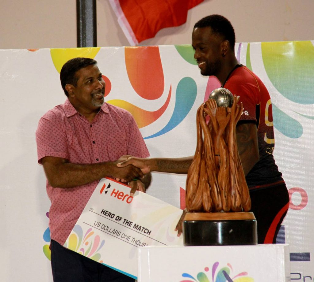 Dinanath Ramnarine, left, presents Kevon Cooper with the Hero of the Match cheque at the CPL final early Sunday morning.