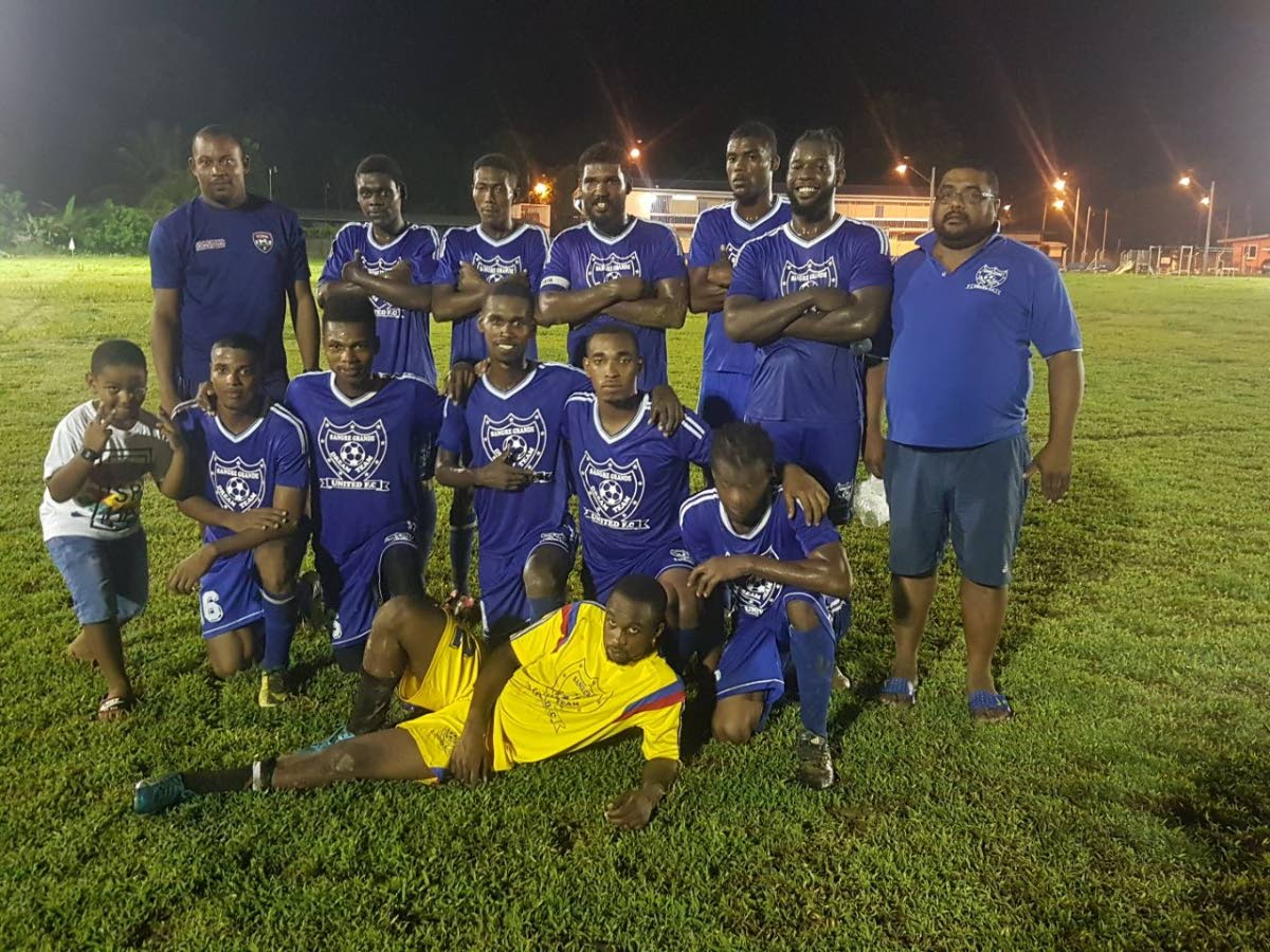 Dream Team players, coach and fans celebrate their victory on Tuesday in the Caribbean Welders Fishing Pond Football League.