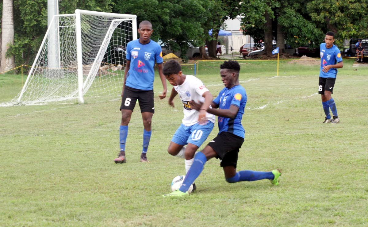 Naparima College's Mark Ramdeen, centre, is marked closely in a Secondary Schools Football League (SSFL) Premier Division match at Lewis Street, San Fernando, yesterday. Naps won 2-0.