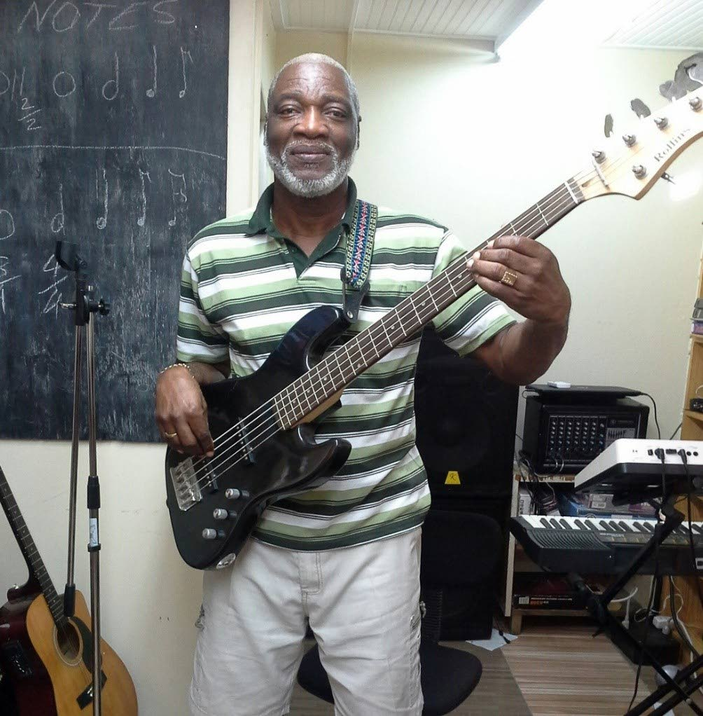 "Curtis John, choirmaster, music teacher and organiser of a ""wake group"" in Bon Accord/Canaan pose for a photo at his music room in Canaan."