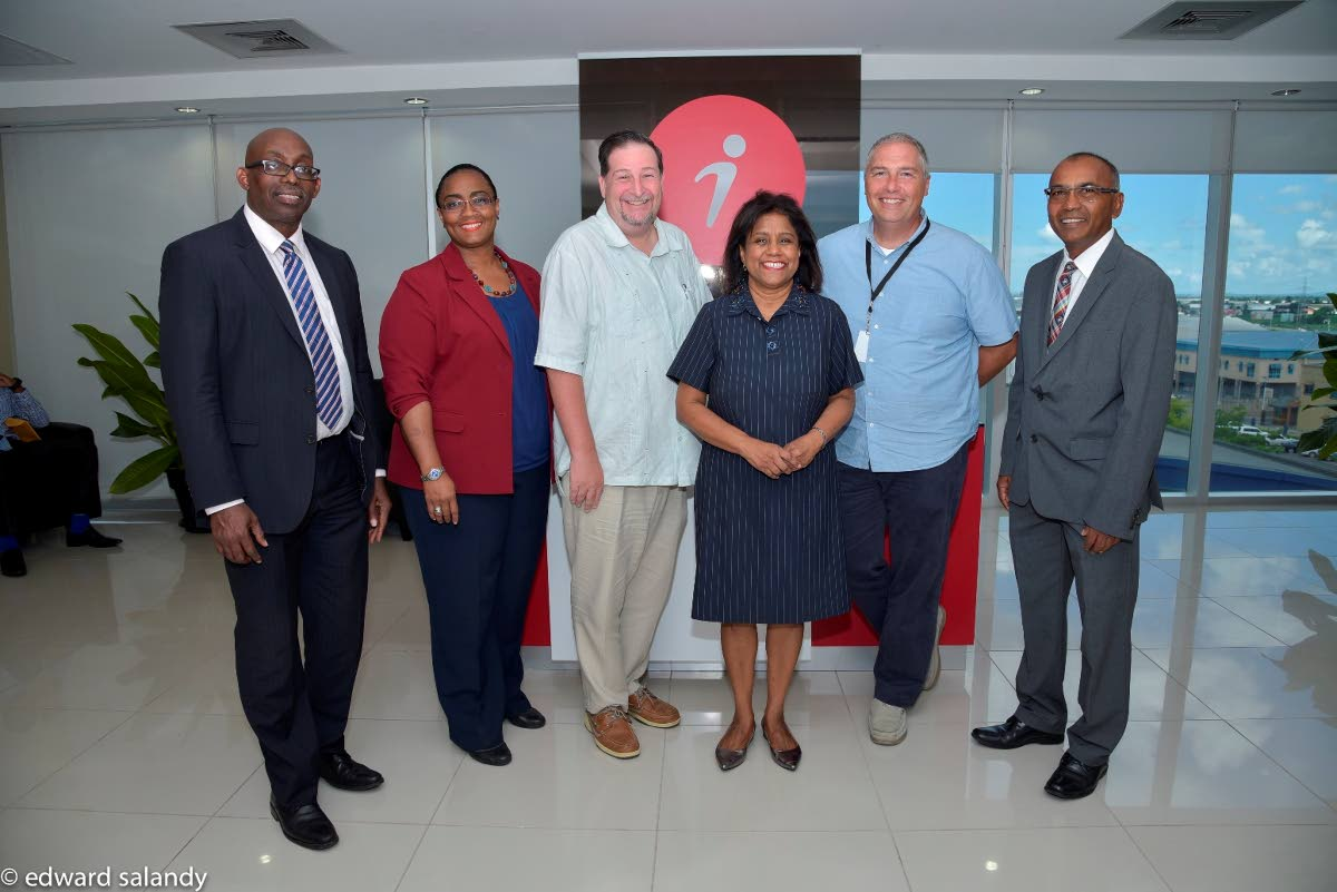 iQor adds 600 jobs to TT:  (Third from left) Trade and Industry Minister, Paula Gopee-Scoon, flanked by John Swain, Director of Operations, iQor (1-800-Flowers), right and Mr. Brian Henderson, Director of Operations, iQor (Metro PCS), left along with Senior Executives, invest Limited. PHOTO COURTESY THE MINISTRY OF TRADE AND INDUSTRY.