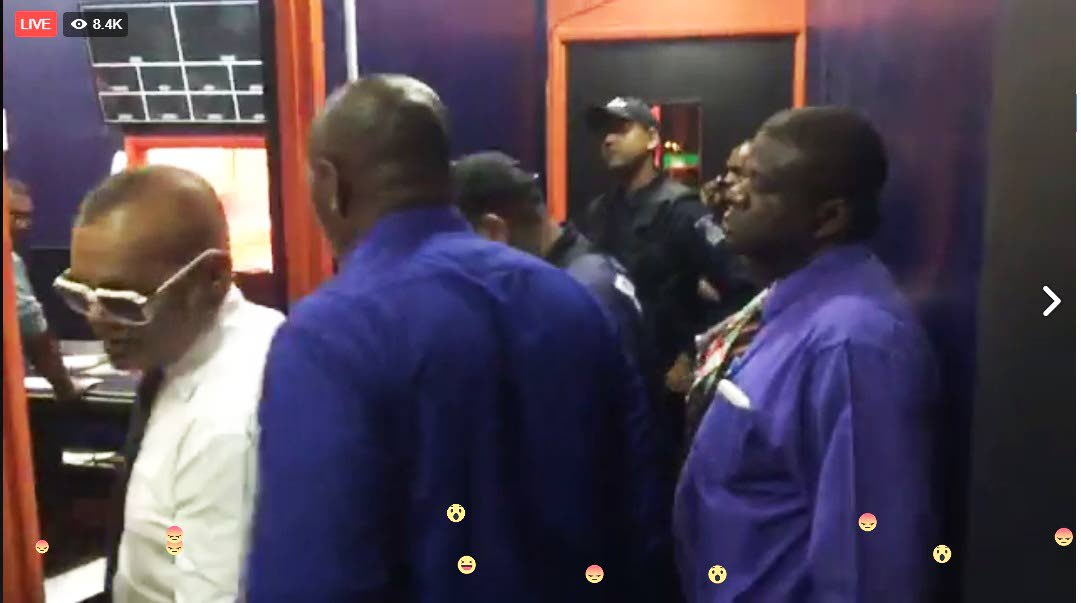 RAID: Crime show host Ian Alleyne, left, walks off as police officers stand outside his studio within the Synergy station office in Chaguanas yesterday.