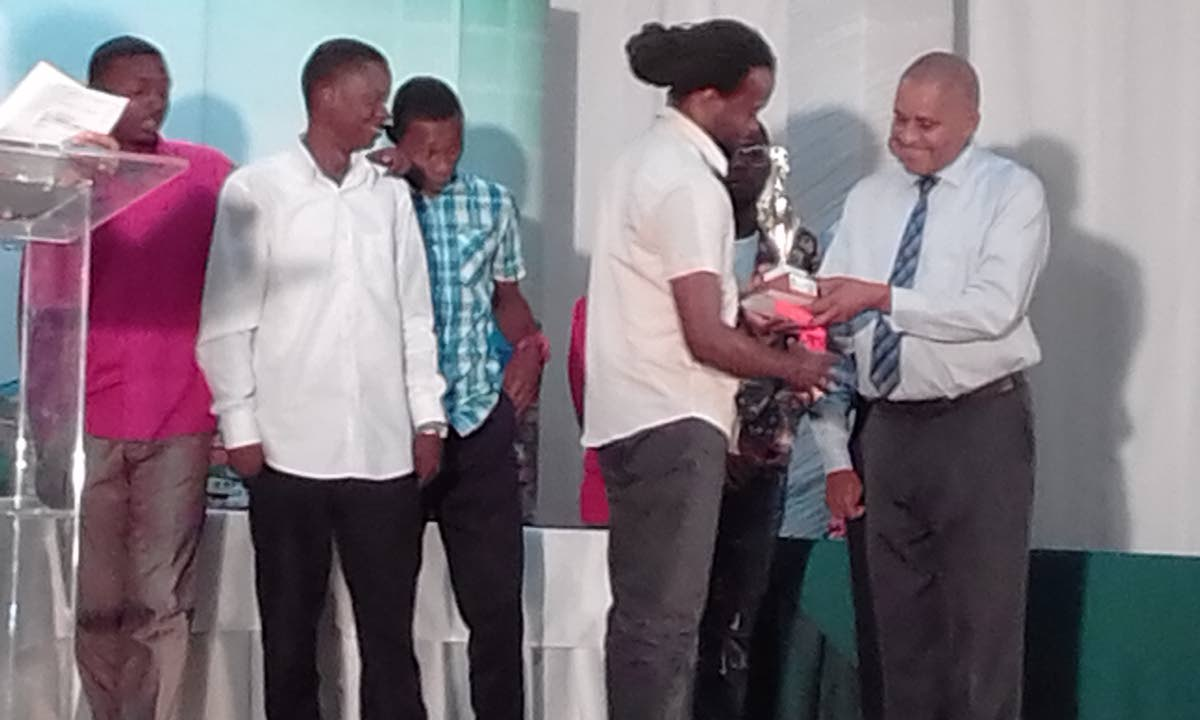 Newman George, chairman of the East Port of Spain Development Company Limited (right), present gold medals and a trophy to members of the BH8 Police Youth Club, after they copped the Open Division Football category.