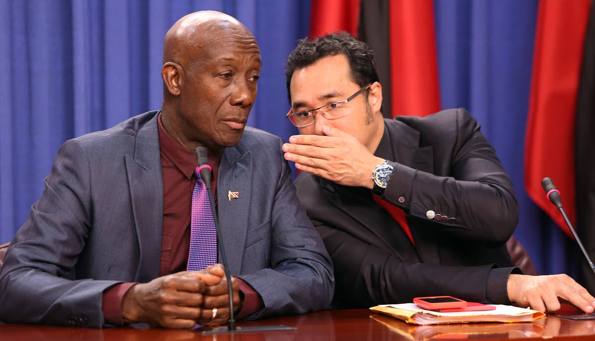 SHOO-SHOOING: Prime Minister Keith Rowley listens as Minister in the Office of the Prime Minister Stuart Young whispers to him yesterday at the post Cabinet press briefing at the Diplomatic Centre in St Ann's.