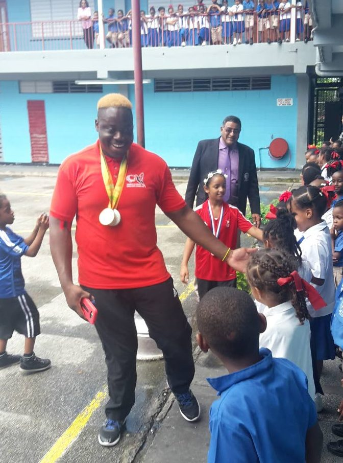 Paralympic gold medallist Akeen Stewart left, greets students at the Sangre Grande Government Primary School during a tour organised by the Sangre Grande Regional Corporation last year.