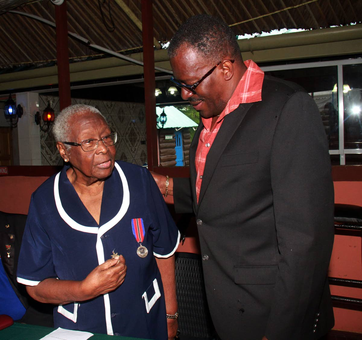 Minister of National Security Edmund Dillon greets World War Veteran Mary Anthony, 91, during a family day of the Southern branch of the Royal Commonwealth Ex-Services League, at Sanderson Heritage Park, Fyzabad.