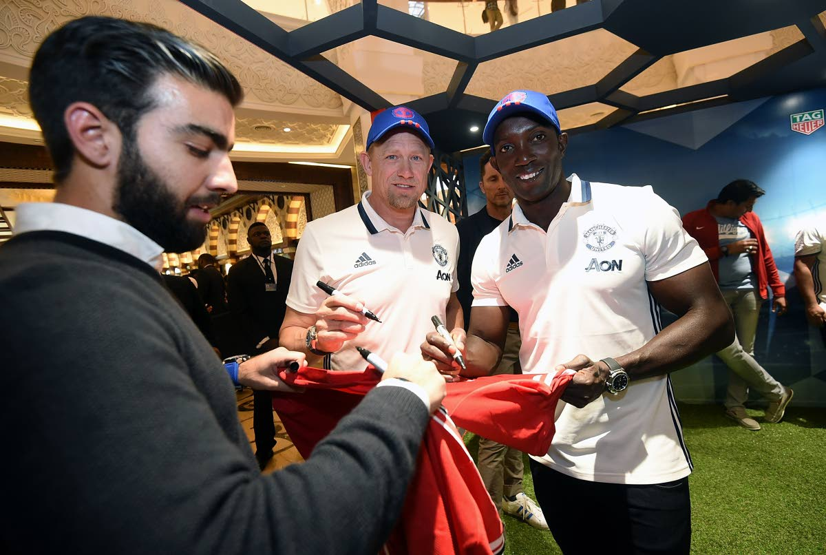 Dwight Yorke (right) and former Manchester United goalkeeper Peter Schmeichel (centre) delight a fan with autographs at a Dubai Mall Tag Heuer event recently.