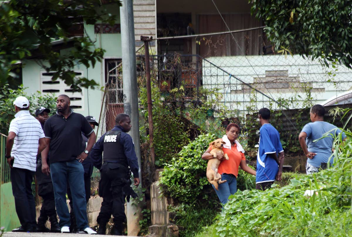 BLOODY SCENE: Police and relatives at Kingston Avenue, La Canoa, Santa Cruz, the scene of the shooting death of Jason Thomas, and three other men who are hospitalised with gunshot wounds.