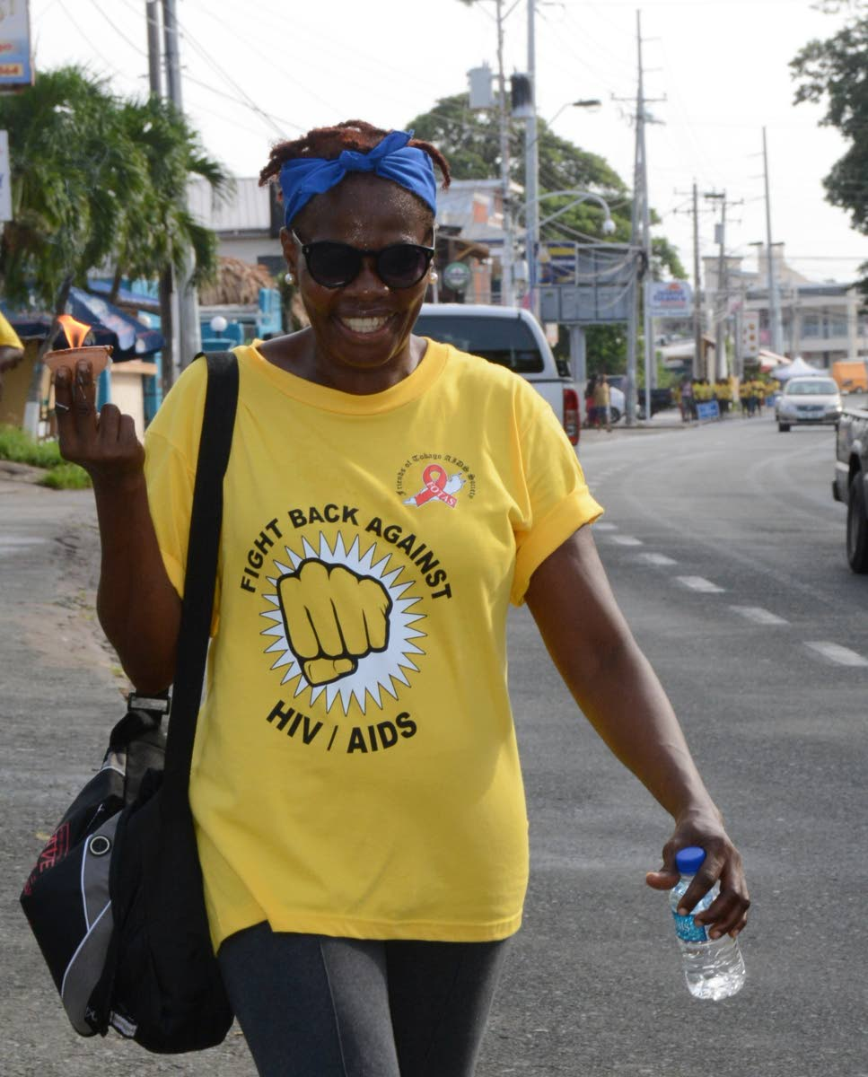 A woman walks with a lighted deya to honour the memory of persons who have died from AIDS as she participated in Monday's Walk against HIV/Aids from the Dwight Yorke stadium in Bacolet to Store Bay, hosted by Friends of the Tobago AIDS Society.