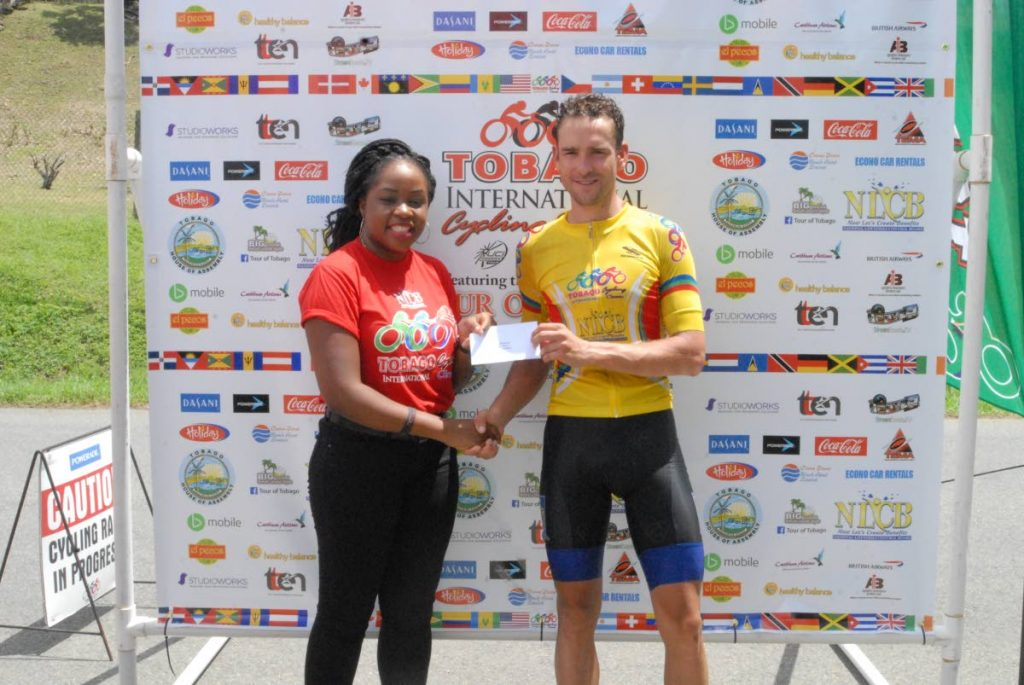 Overall winner of Division One of Stage Two, Peter Schulting, (right) collects his prize from NLCB Director Ria Joseph at Old Grange Bay, Mt Irvine yesterday. PHOTO COURTESY TICC