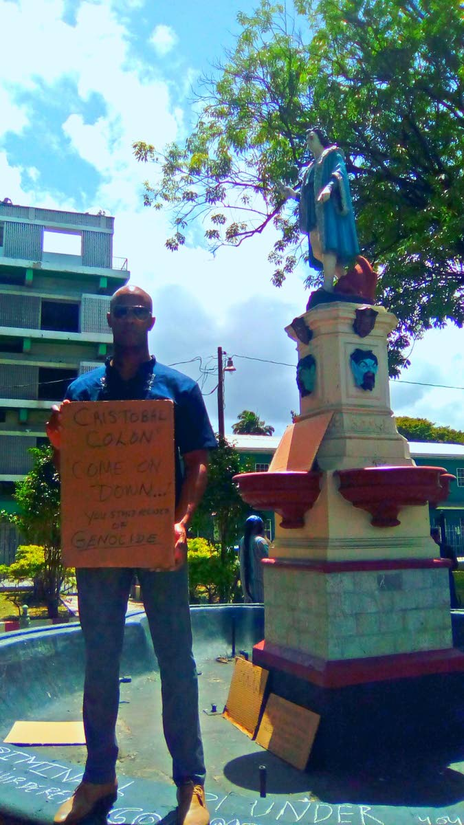 Shabaka Kambon, coordinator and founder of the Cross Rhodes Freedom project stands with a picket sign near Columbus statue in downtown Port-of-Spain yesterday. Kambon is calling for a removal of the statue and an end to a 'whitewashing' of history in T&T. PHOTO BY SHANE SUPERVILLE
