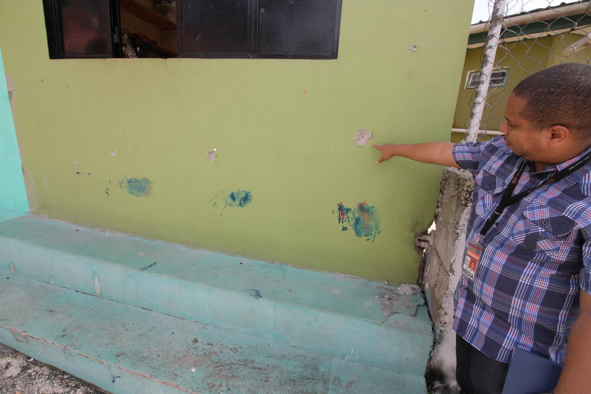 WILD WILD EAST POS: Newsday reporter Julien Neaves points to bullet holes on the front of a parlour at Plasiance Quarry Road, John John, Laventille. The bullets were from an exchange of gun fire between police and gunmen on Friday night.