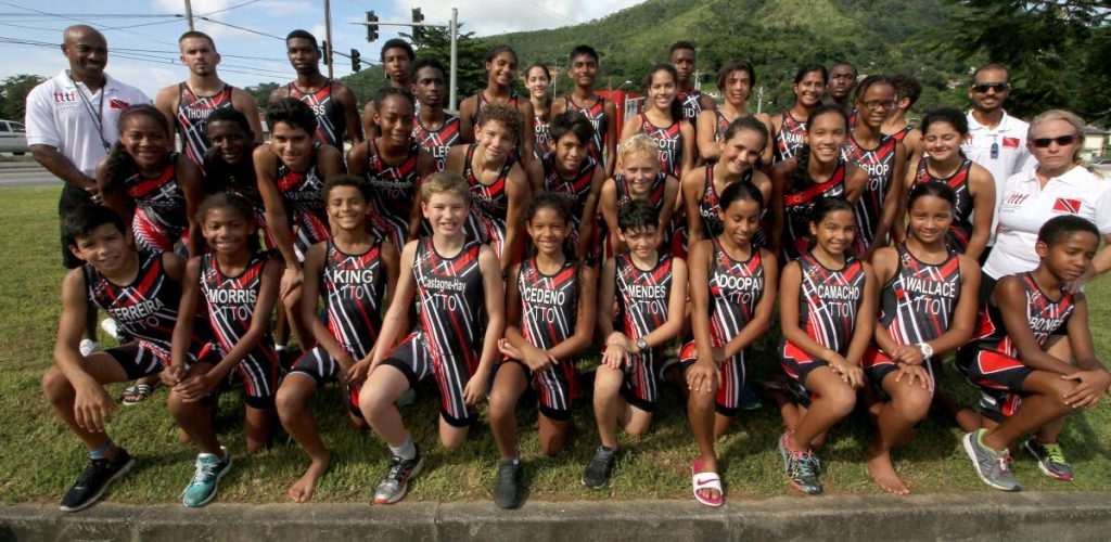 """The national triathlon team including coaches take a photo at their final training session yesterday at the """"Keep Fit Sundays"""" circuit of the Diego Martin Highway."""