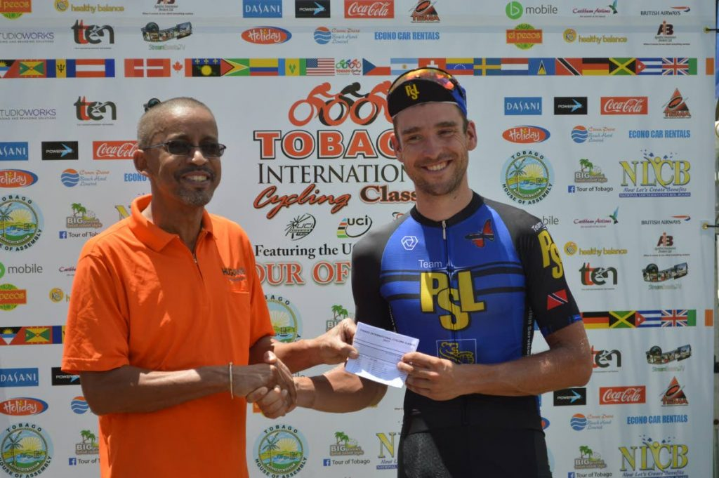 Winner of the 2017 UCI 1.2 Tour of Tobago title Peter Schulting of Netherlands/PSL (right) collects his winning prize from Nigel Wilson, Tourism Officer of the Division of Tourism, Culture and Transportation of the Tobago House of Assembly, at the end of the race at the Scarborough Esplanade, Milford Road, Scarborough yesterday. PHOTO COURTESY TICC.