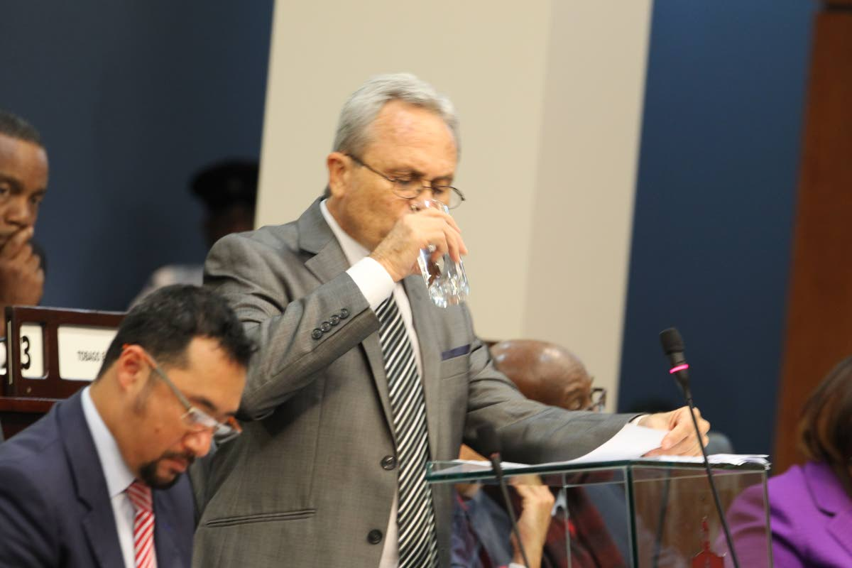 I'LL DRINK TO THAT: Finance Minister Colm Imbert quenches his thirst during his 2018 Budget presentation in the House yesterday.