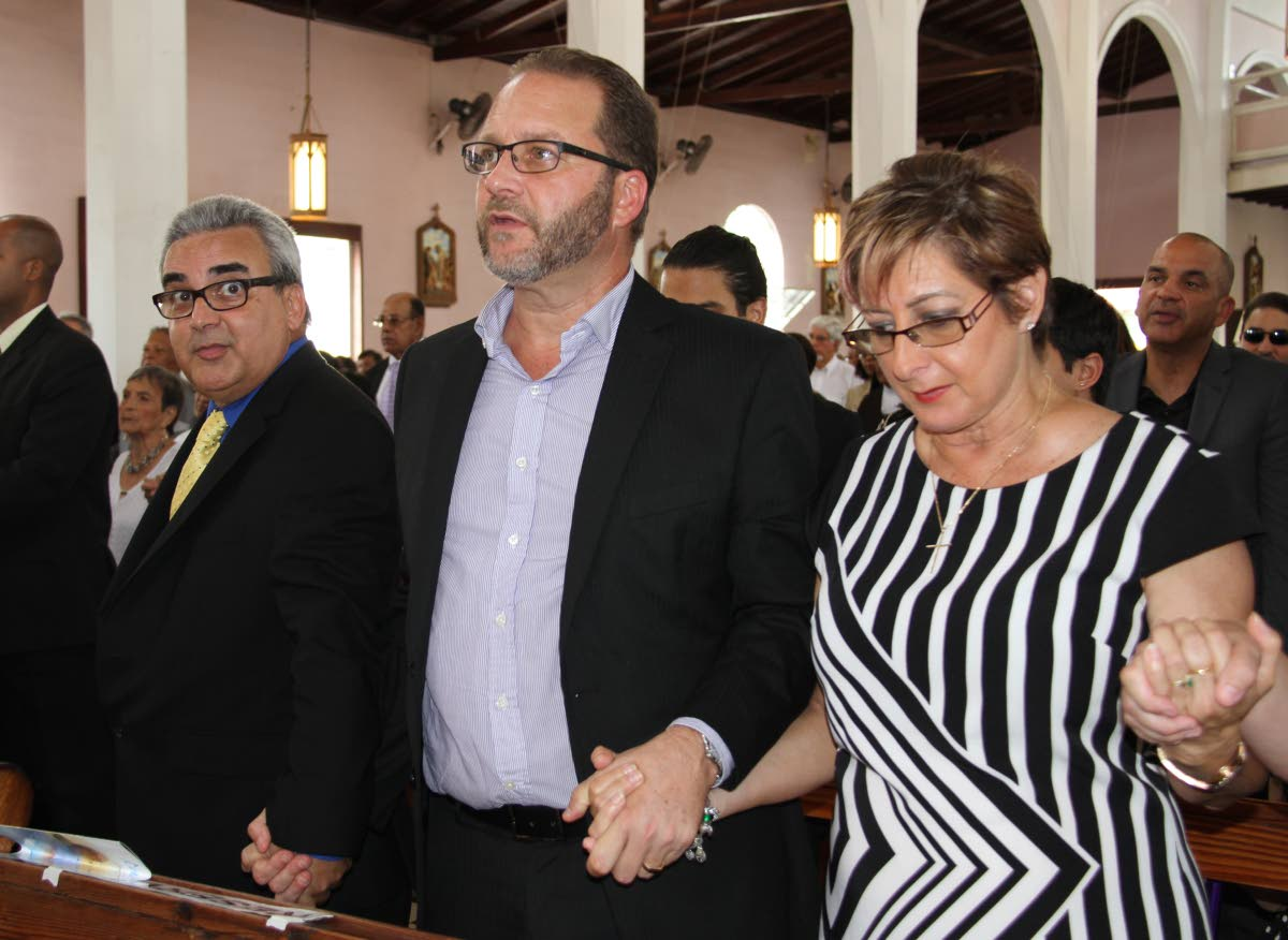 GOODBYE DADDY: (left to right) Bernard , Thomas and Anna Pantin join hands at the funeral for their father, former Fatima principal and  Minister of Education, Clive Pantin. Pantin was 84.
