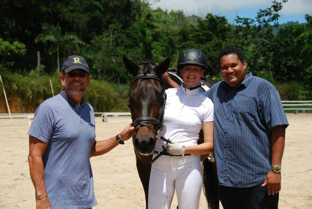 Sports Minister Darryl Smith (right) pose for a photo alongside TTEA president Duglas Watsun (left) and rider Amy Costelloe with horse Claudio.