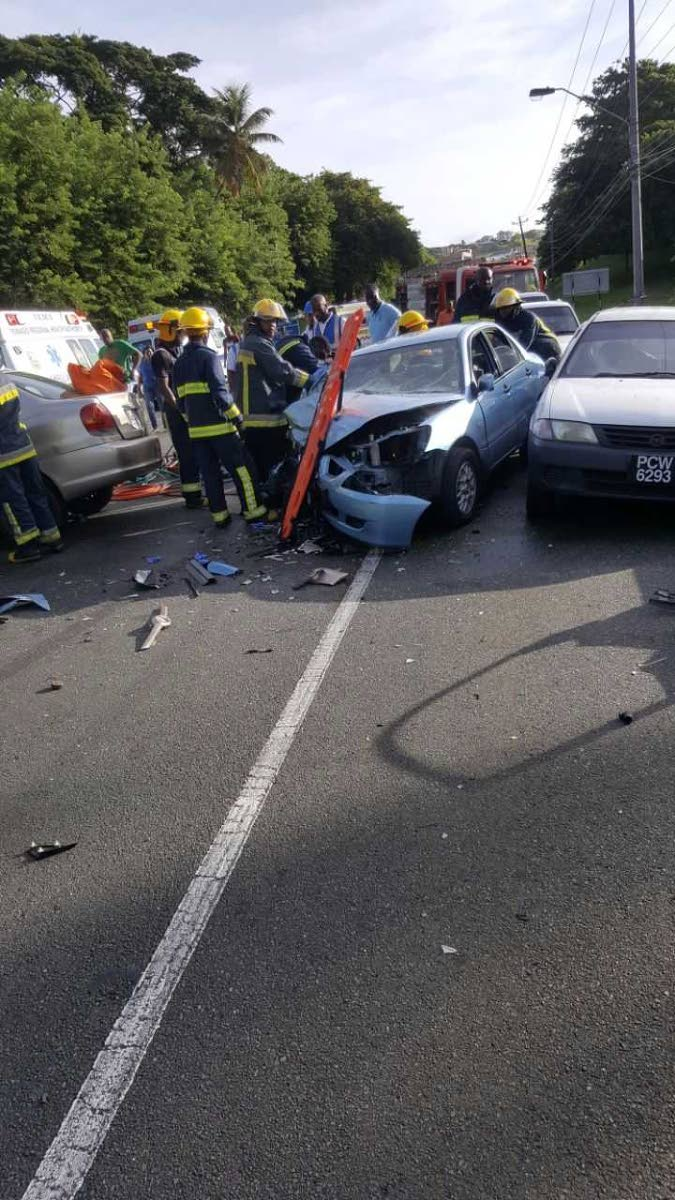 DEADLY CRASH: Firemen, near to the Signal Hill intersection, Tobago gain entry to a smashed Mitsubishi Lancer, which was driven by Mohammed Khan ,85, on Monday morning when he was involved in an accident which claimed his life.