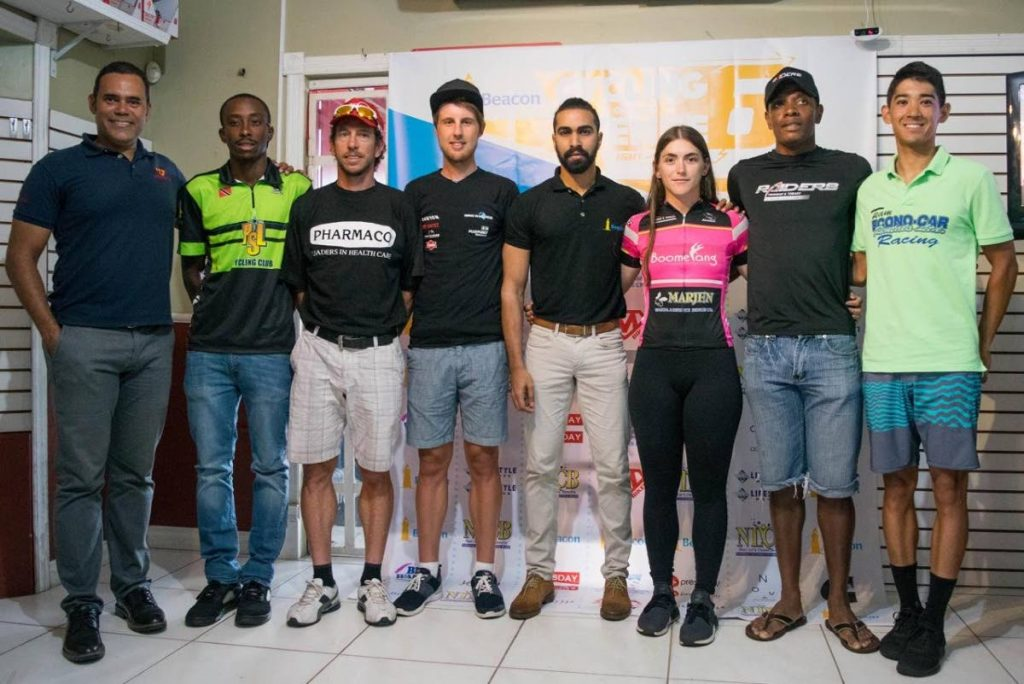 Race promoter Michael Phillips, left, Beacon representative Kevin Siewdass, fourth from right, and cyclists at a press conference at Mike's Bikes, yesterday.