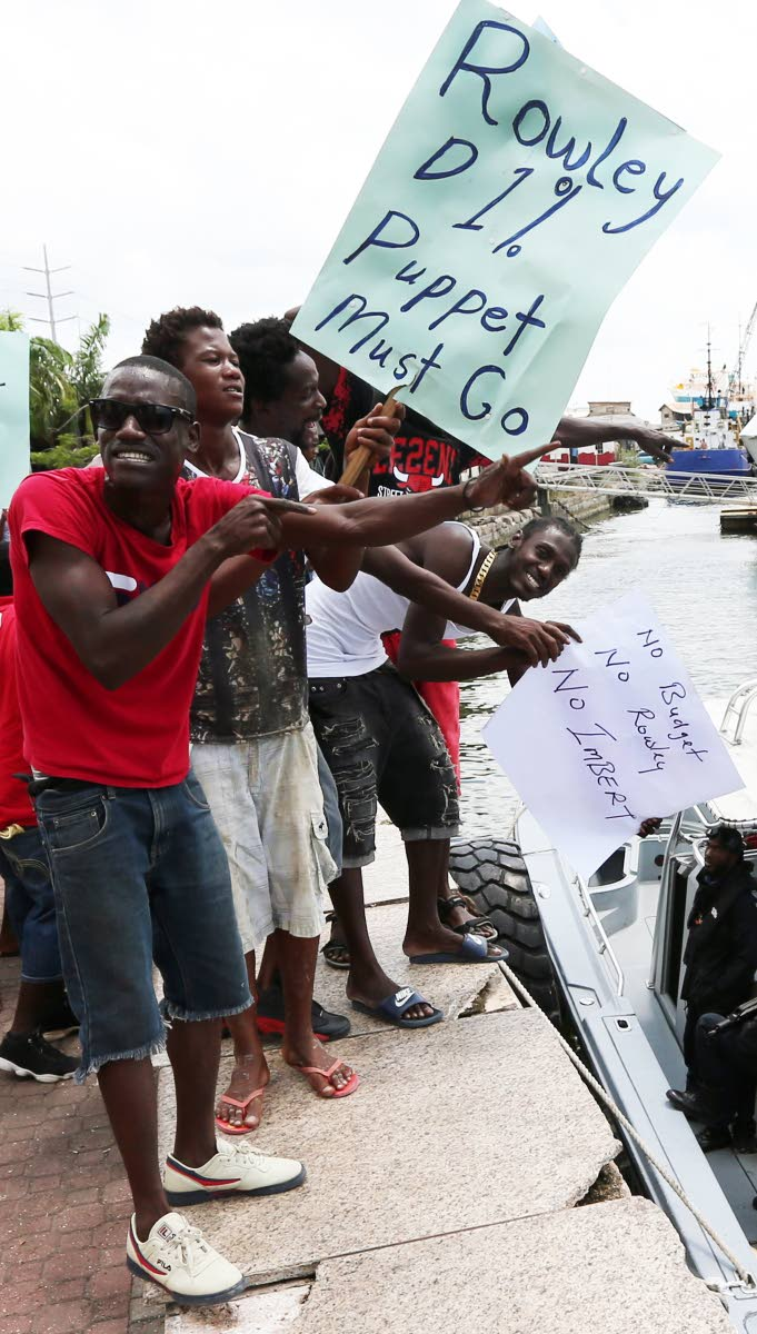 PROTESTING FUEL HIKE: Fishermen protest at the International Waterfront Centre in Port of Spain yesterday over the increase in fuel prices. PHOTO BY AZLAN MOHAMMED