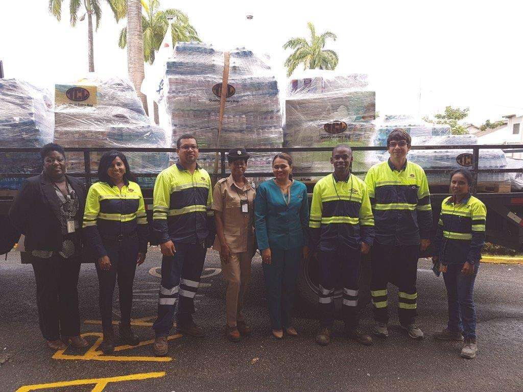 TCL employees standing in front of relief items for Dominica.
