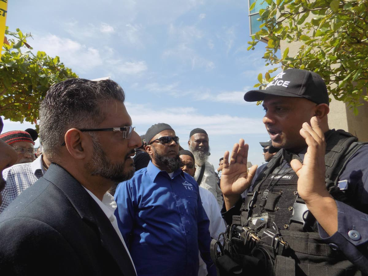 Former government Minister Devant Maharaj clashes with an officer from the Guard and Emergency Branch outside Tower D of Parliament at the International Waterfront in Port of Spain yesterday, as officers attempted to prevent protestors from gathering outside the chamber entrance.