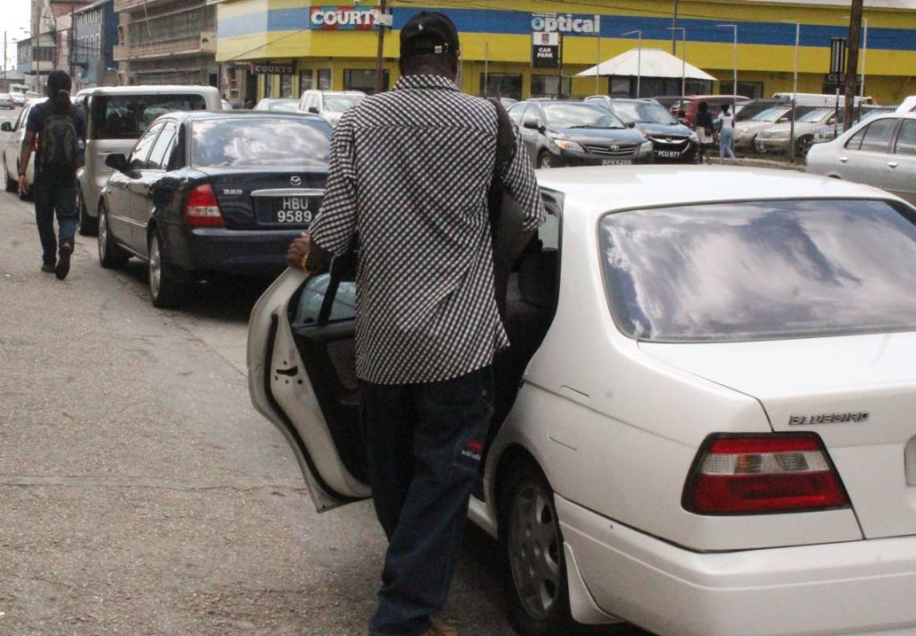 In this file photo, a passenger enters a taxi on the Diego Martin/Petit Valley stand in Port of Spain.