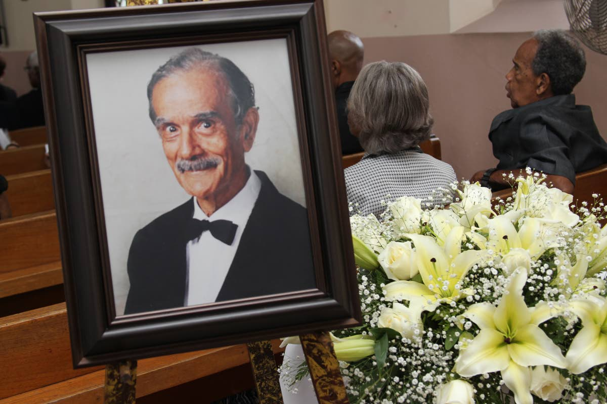 In memorium: Mourners sit near a portrait of retired Chief Justice Cecil Kelsick at his funeral. PHOTO BY RATTAN JADOO
