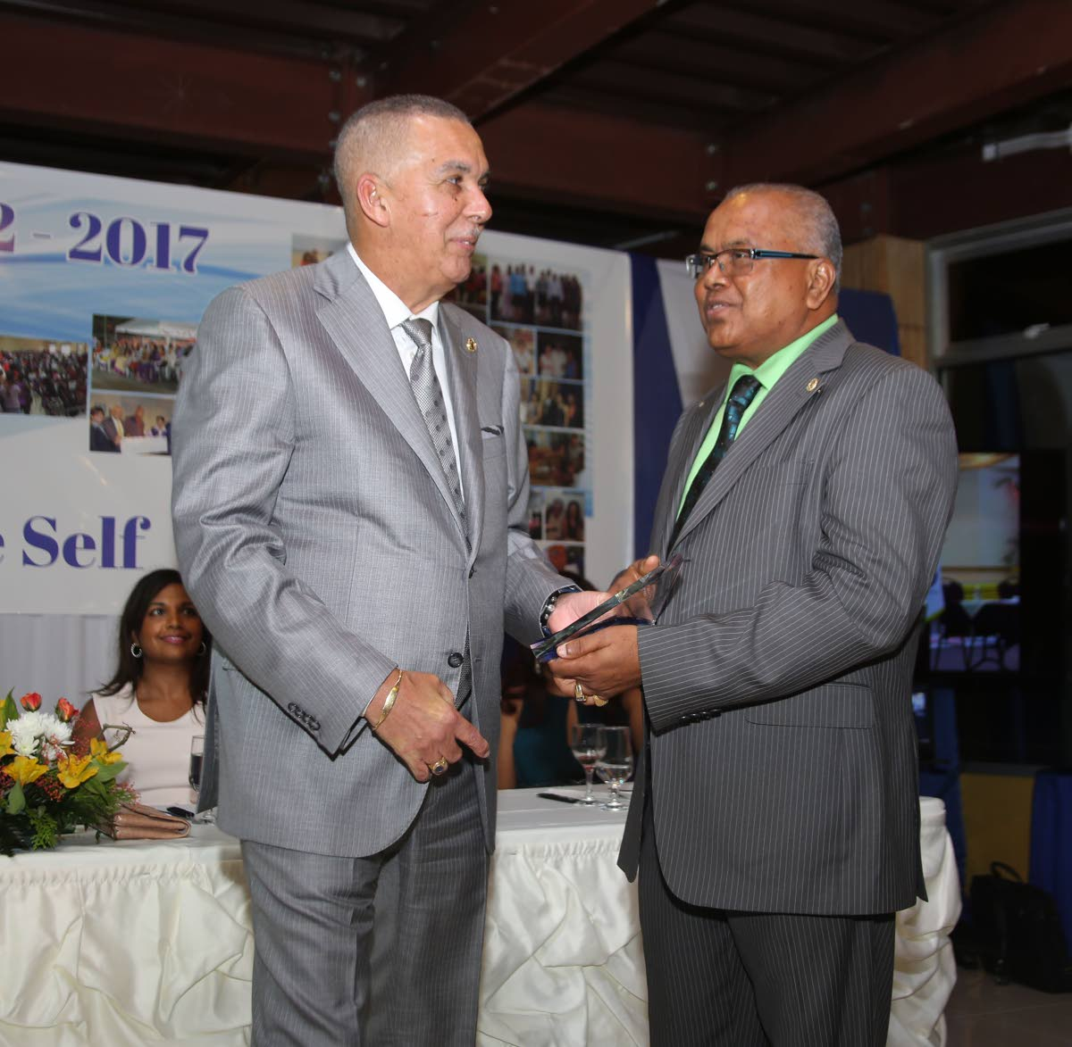 Suruj Mangaroo of the Rotary Club of Penal presents President Anthony Carmona, left, with an award during the Club's 15th anniversary celebrations at Doc's Ranch in Phillipine on the weekend.