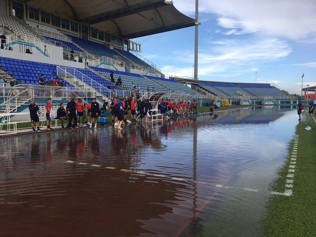 USA team officials and players contemplate whether to walk through the flooded track area to get to the field at the Ato Boldon Stadium in Couva this morning. PHOTO COURTESY US SOCCER