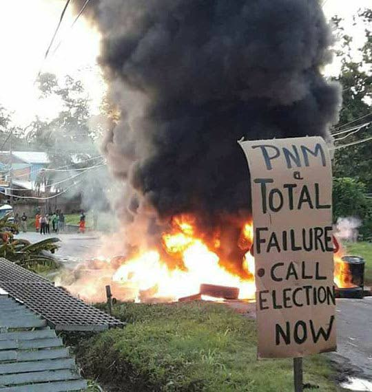 ROAD ON FIRE: Residents of Mayaro and Rio Claro burn debris used to block a road as they protest the increase in fuel prices announced recently and the deplorable road conditions in their areas.