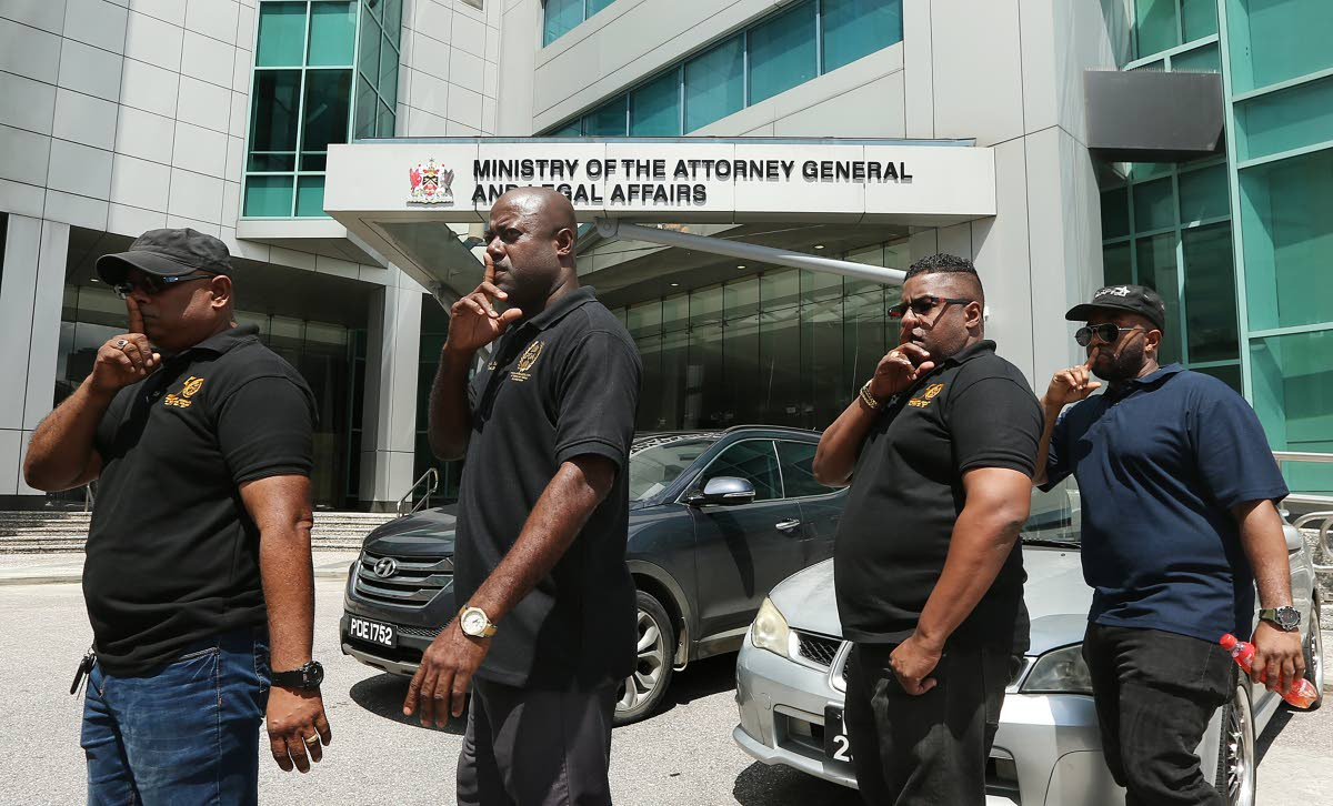 SILENCE: Members of the Prison Officers Association led by president Ceron Richards, right, in a silent protest outside the Office of the Attorney General in Port of Spain yesterday following the murder of a prison officer on the weekend. PHOTO BY AZLAN MOHAMMED