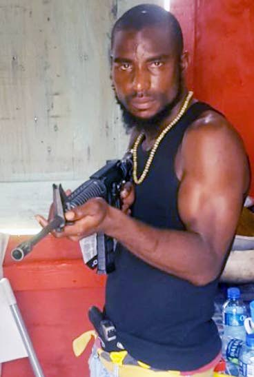 A photo, purporting to show Tai 'Monster' Branker brandishing a rifle was posted to social media in the wake of him being shot dead on Monday evening in Claxton Bay.