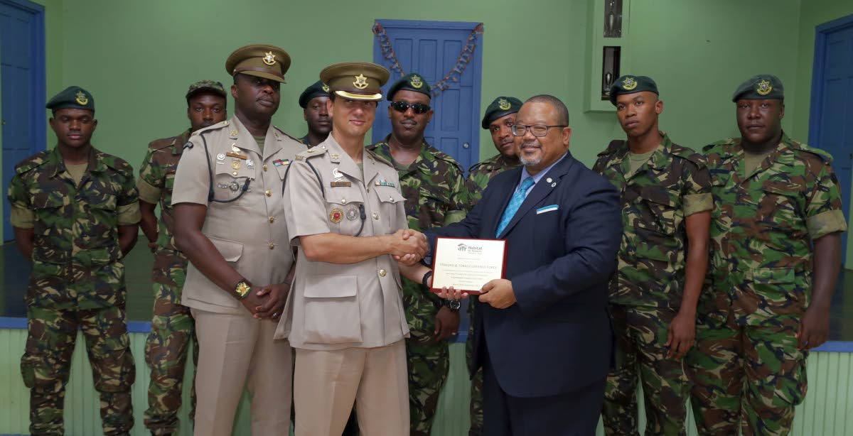 Commanding officer of the Regiment's First Engineering Battalion, Major Jerome Affonso, receives an appreciation award on behalf of soldiers who worked alongside volunteers on the 'Safe Shelter Through Landslide Mitigation' project in Moriah from Derwin Howell,chairman of Habitat for Humanity Trinidad and Tobago.
