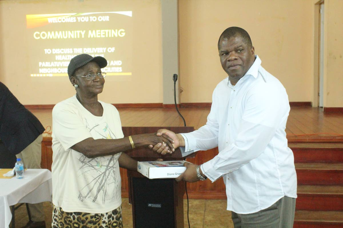 Carlos Waldron, Director of Finance, TRHA, presents a 211 Emergency Medical Alert System to Mary Plante, on behalf of her sister Diana Grant at a community meeting at the Parlatuvier community centre last Tuesday.