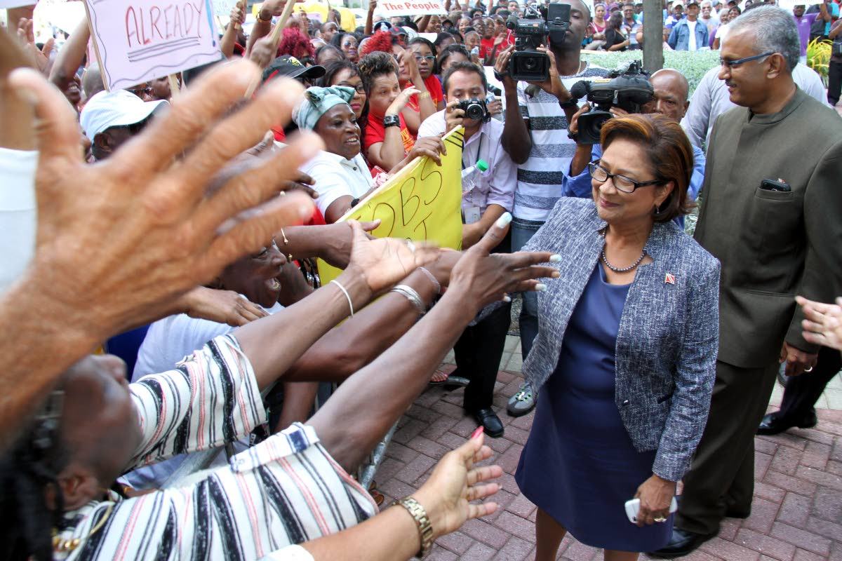Opposition Leader Mrs Kamla Persad-Bissessar greets demonstrators outside Parliament yesterday. Persad-Bissessar told demonstrators they will be given a voice in the Senate to voice their concerns on the budget. PHOTO BY SUREASH CHOLAI