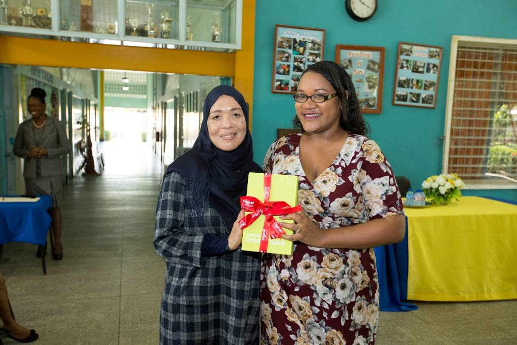 Zippy's Friends 2016-2017 Teacher of the Year Samantha Sooknanan (right) shares the moment with her co-worker at the St Augustine South  Primary School.