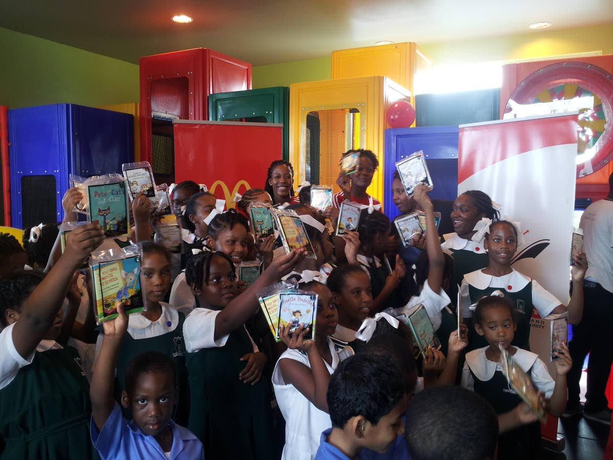 TT women's volleyballers Jelicia Ross and Channon Thompson, back, at the McDonald's/NALIS Happy Meal Books programme launch at McDonald's, Cipriani Boulevard, yesterday.