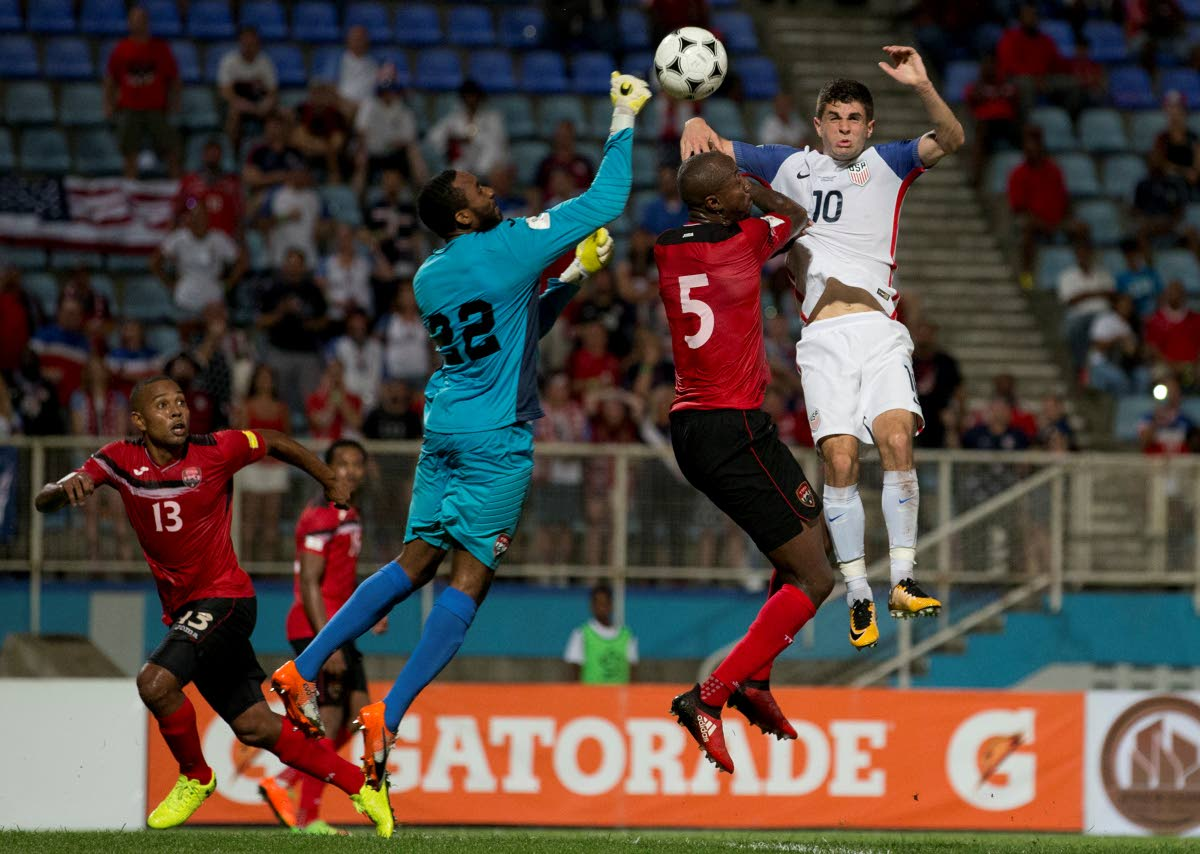 Trinidad and Tobago goalie Adrian Foncette, centre, punches the ball away from danger in a 2018 World Cup qualifier against USA on Tuesday at the Ato Boldon Stadium, Couva.