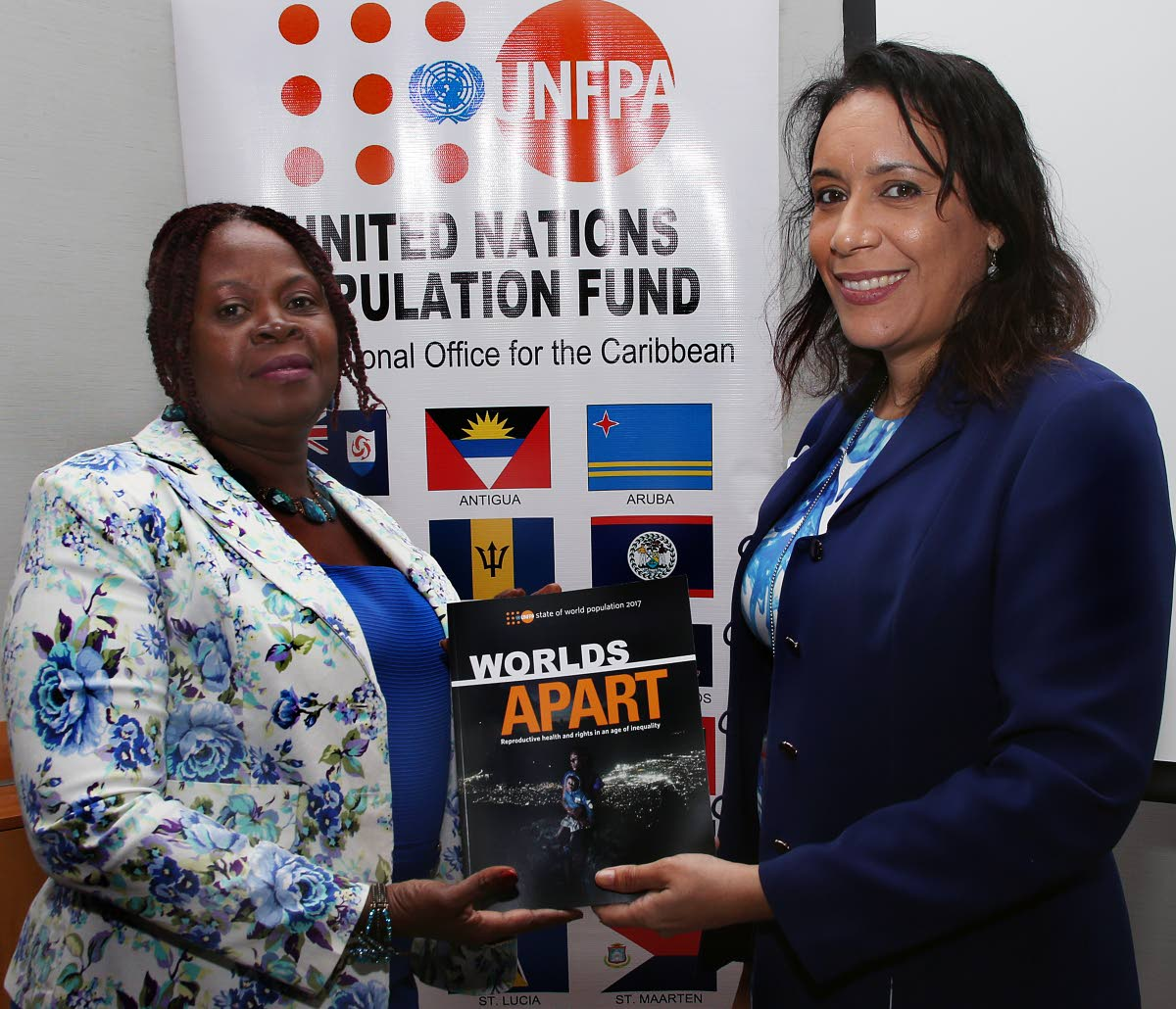 At right, UNFPA liaison officer Aurora Noguera - Ramkissoon presents a copy of the 2017 report tiled 'Worlds Apart